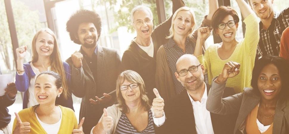 A imagem mostra colaboradores de diferentes idades, gêneros e raças. Todos estão fazendo um sinal positivo com as mãos, demonstrando ânimo.