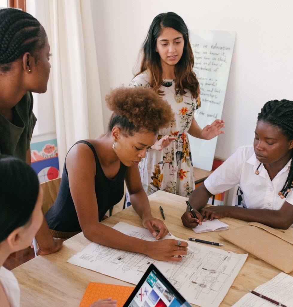 A imagem revela uma reunião de trabalho, com três mulheres negras e duas mulheres brancas,com 5 pessoas discutindo sobre um projeto em cima de uma mesa, que está ao centro.