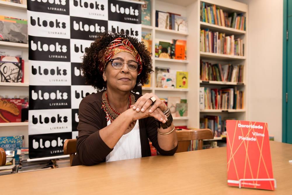 """A imagem é uma foto da escritora Vilma Piedade, sentada em uma mesa de autógrafos no lançamento do seu livro """"Dororidade""""."""