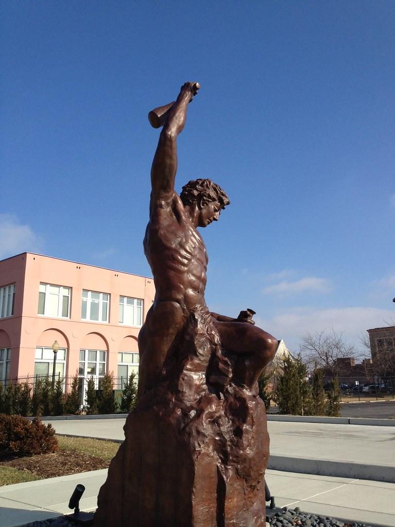 A imagem é uma foto da escultura da artista Bobbie Carlyle, que descreve o self-made man, um homem lapidando a si mesmo para fora da pedra bruta.